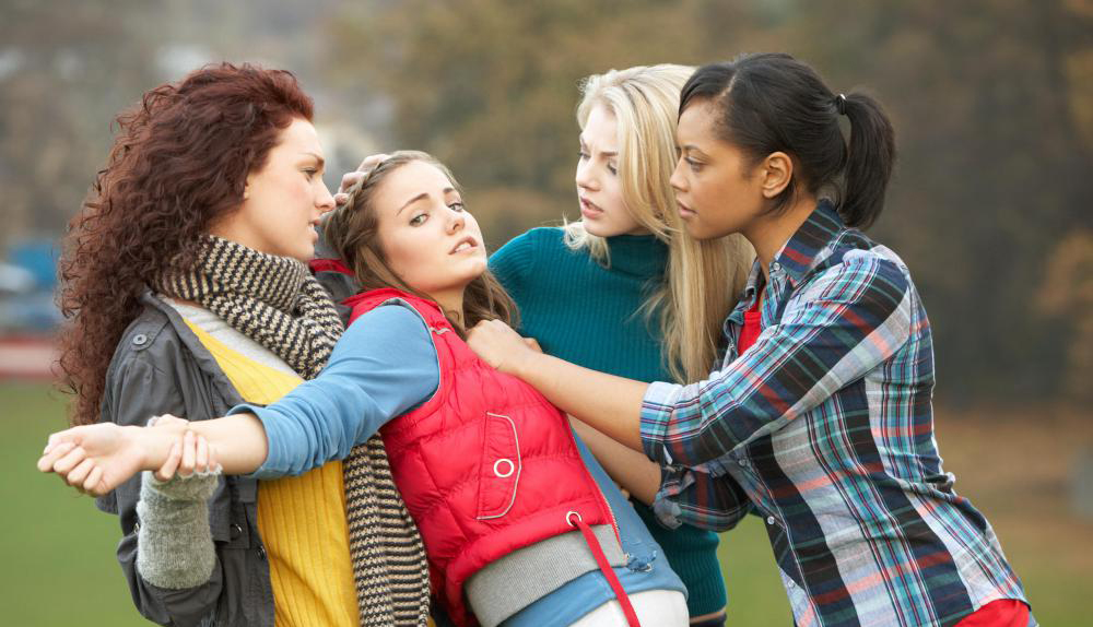 three-girls-ganging-up-on-one-girl-in-red-vest